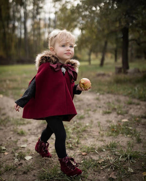 girl wearing burgundy cape witu faux fur hood