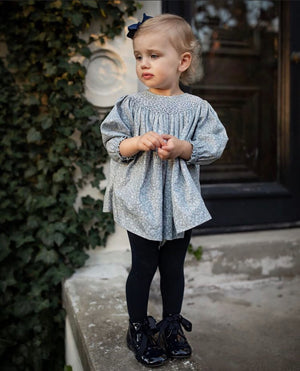 girl wearing spanish hand smocked baby outfit in blue