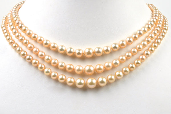 A necklace classic three-strand apricot graduated pearls