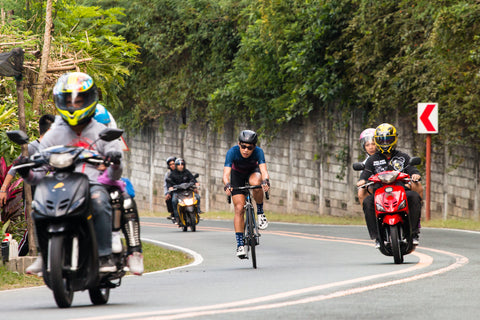 A cyclist riding through an uphill slope with motorcycles
