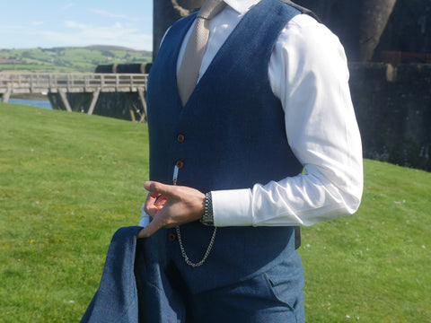 Man holding a blue herringbone tweed Jacket and wearing a tweed waistcoat and trouser