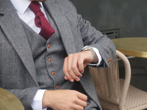 Man wearing a grey suit checking the time
