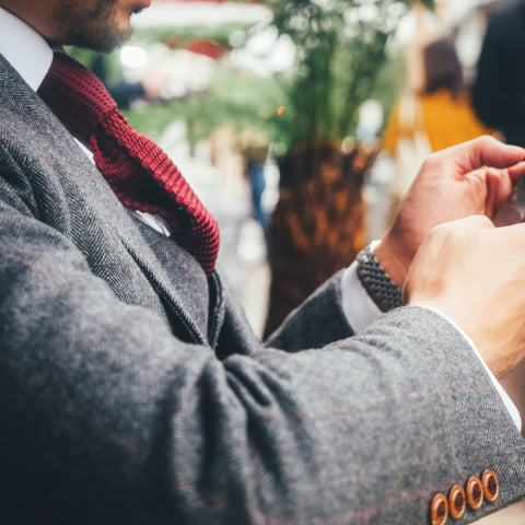 Man wearing a grey suit and browsing the web on his phone