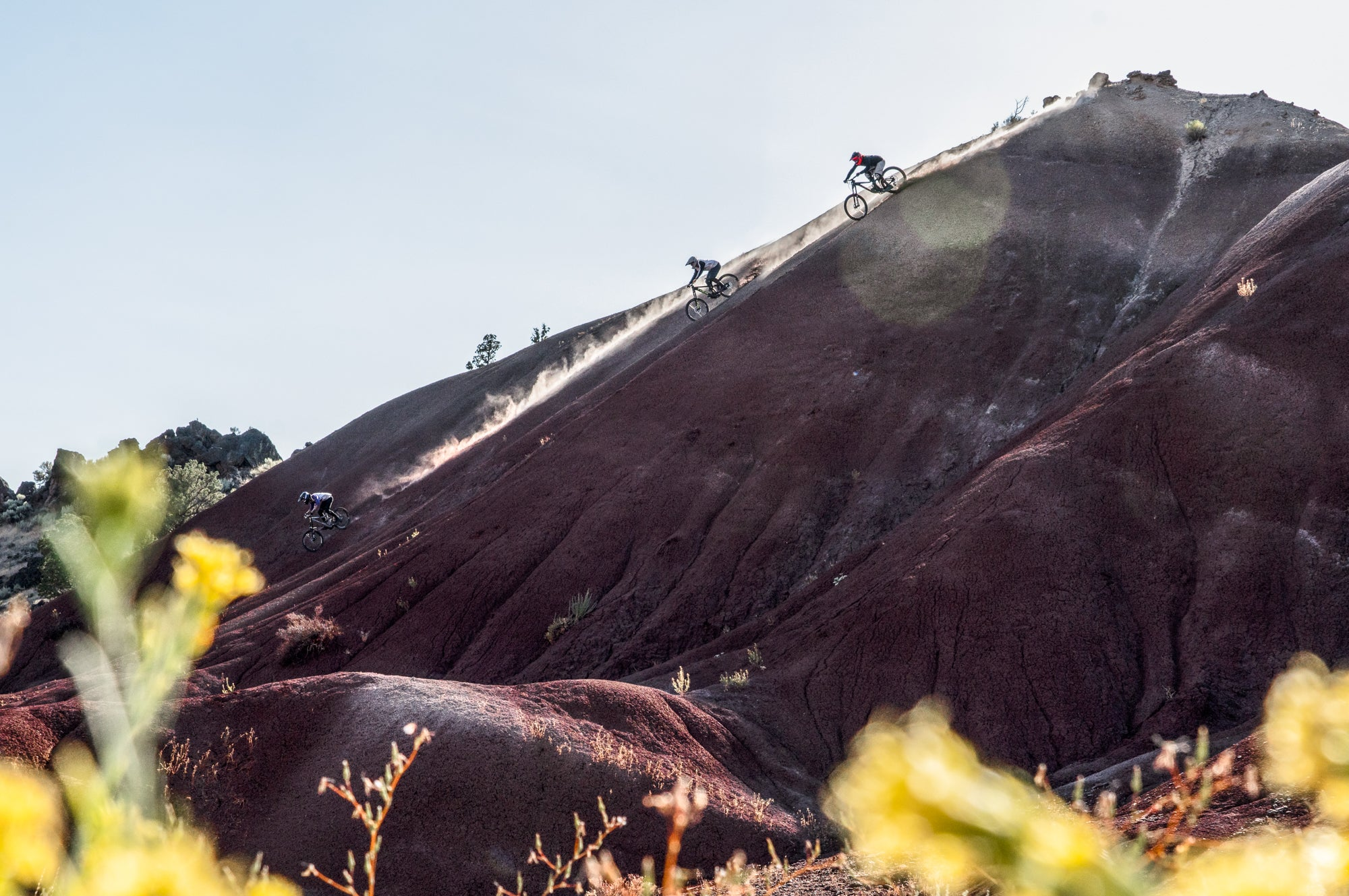 Multiple Mountain Bikers Riding Down a Mountain Spine