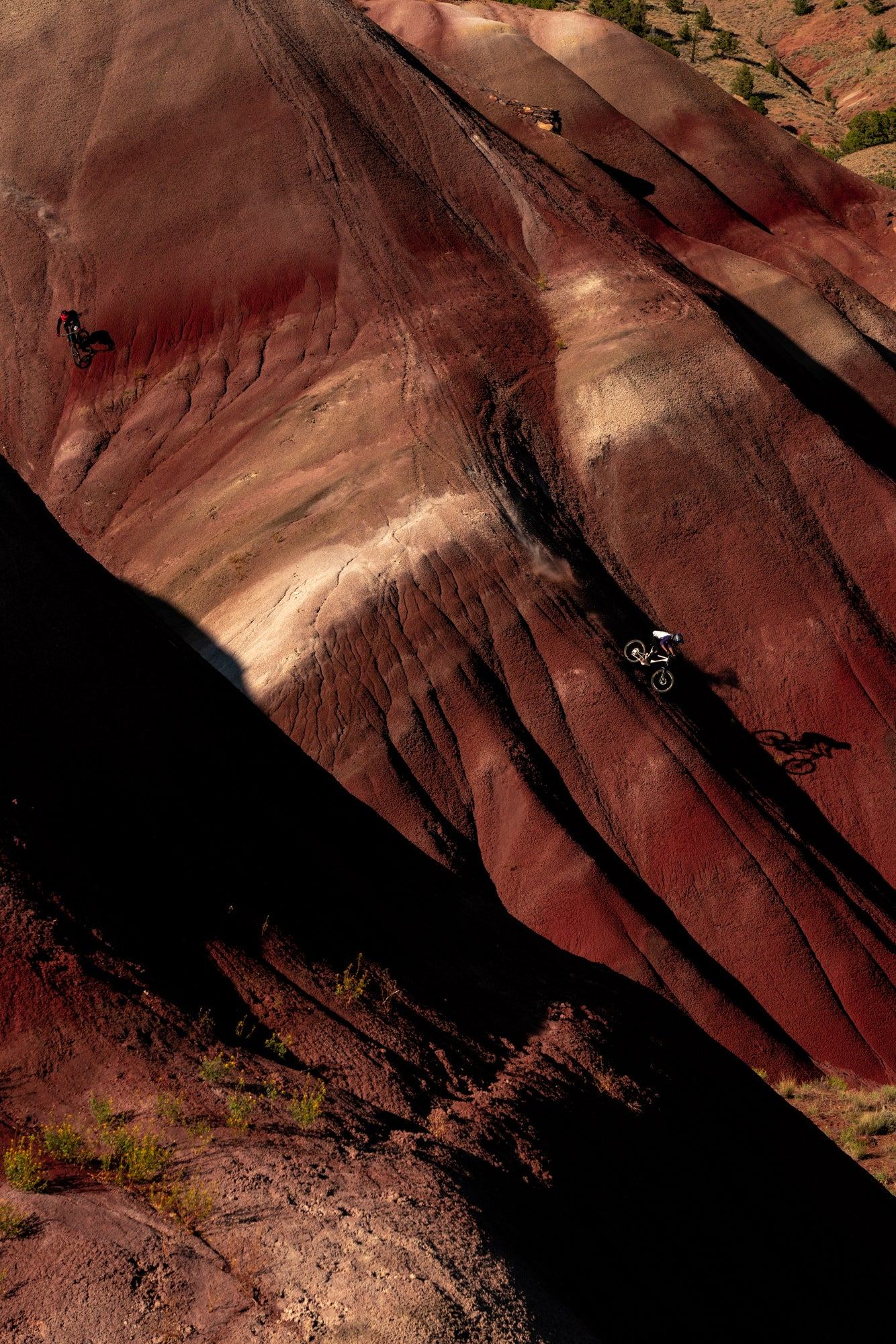 Mountain Biker Riding Down a Red Dirt Spine
