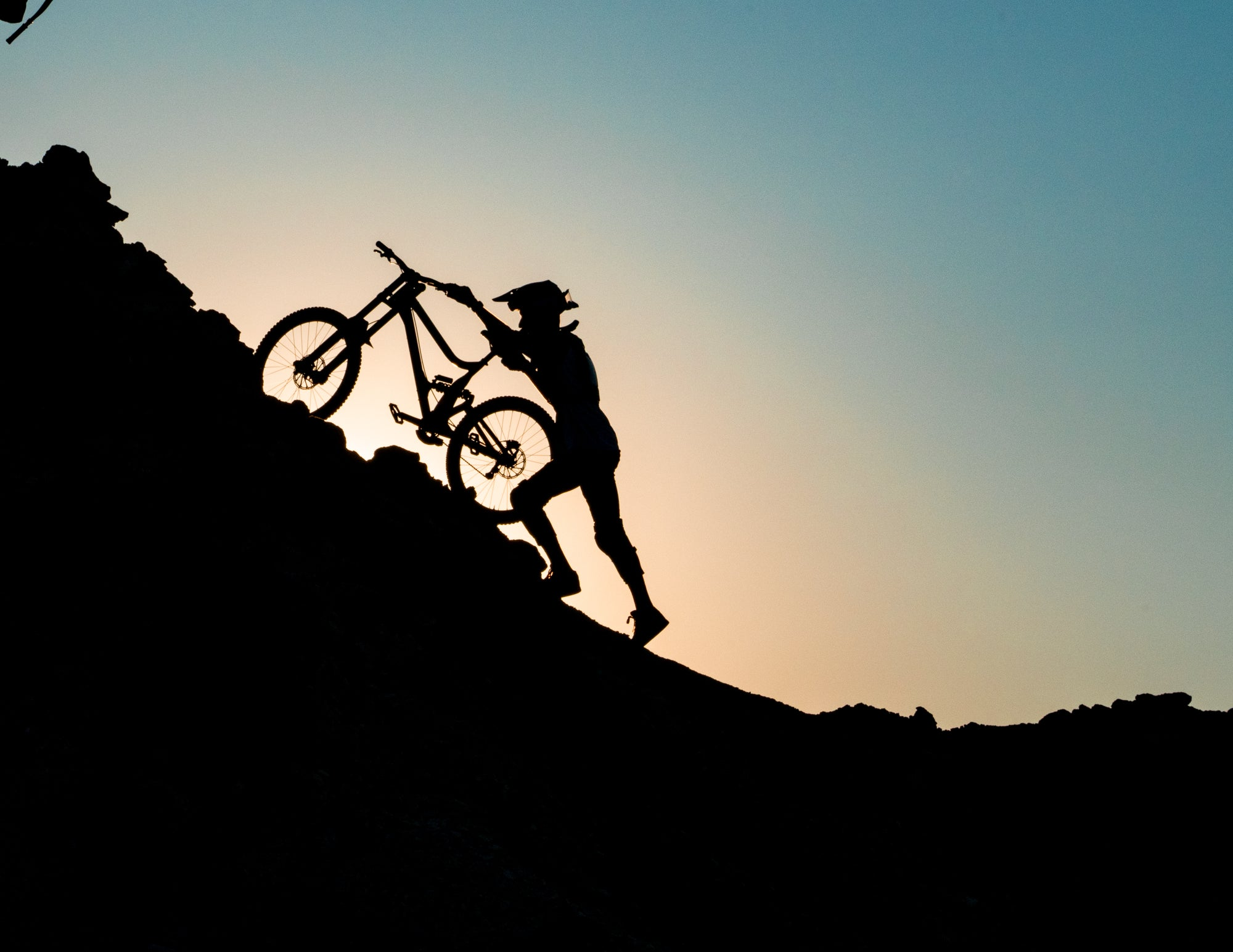 Mountain Biker Pushing Bike Up Mountain