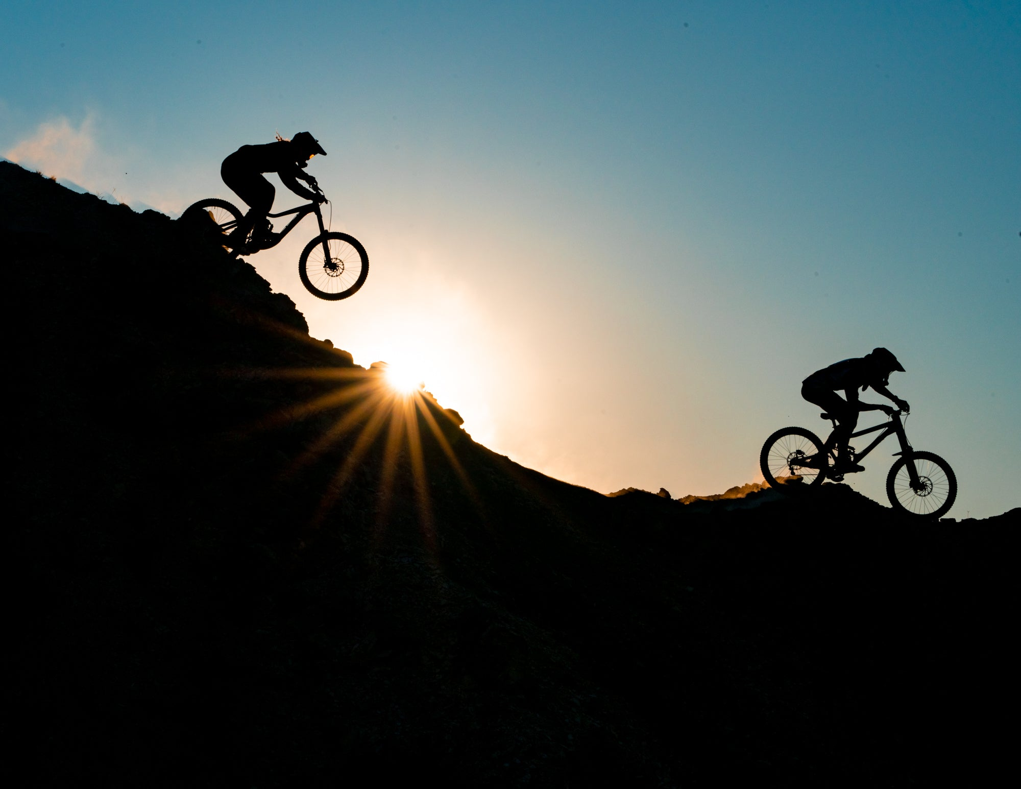 Two Mountain Bikers Riding Down a Mountain Spine at Sunset