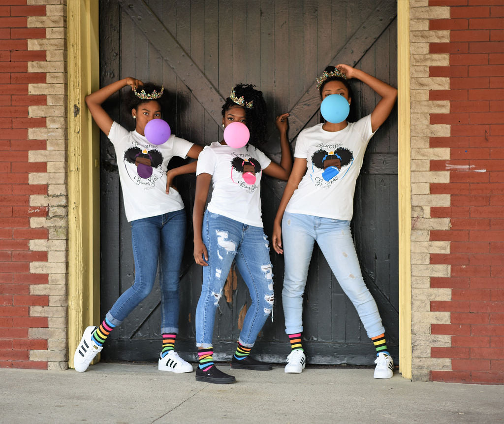 Three Beautiful Brown Queens blowing bubbles and wearing our Classic BeYOUtiful Brown Girl Project shirts.