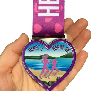 purple and pink running medal in the shape of a heart with two runners and scenic ocean background in a women's hand