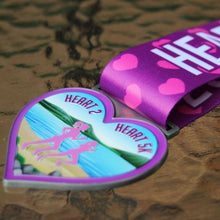 Load image into Gallery viewer, purple and pink running medal in the shape of a heart with two runners and scenic ocean background laying on table
