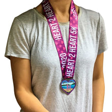 Load image into Gallery viewer, women wearing a purple and pink running medal in the shape of a heart with two runners and scenic ocean background and purple ribbon that says heart 2 heart 5K