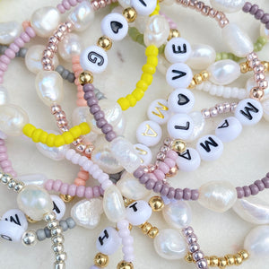 Shop stacking bracelets from The Lovely Edit with a range of handmade personalised pearl bracelets, freshwater pearls, letter bracelets, word bracelets, name bracelets, gold stacking bracelets, sterling silver bracelets, semi precious stones.