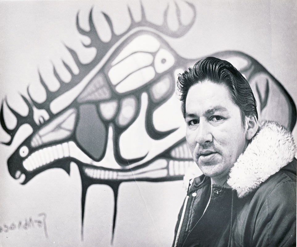 young morrisseau portrait standing infront of his original painting featuring a woodland art style moose