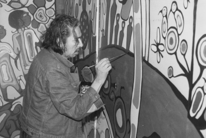 Norval Morrisseau mid aged kneeling down and painting a very large mural