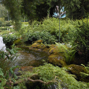 Pond landscape with thriving greenery and a lyman whitaker kinetic wind sculpture copper spinner for landscape design and company enjoyment.