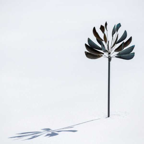 copper wind powered spinner in the snow with shadow for garden art