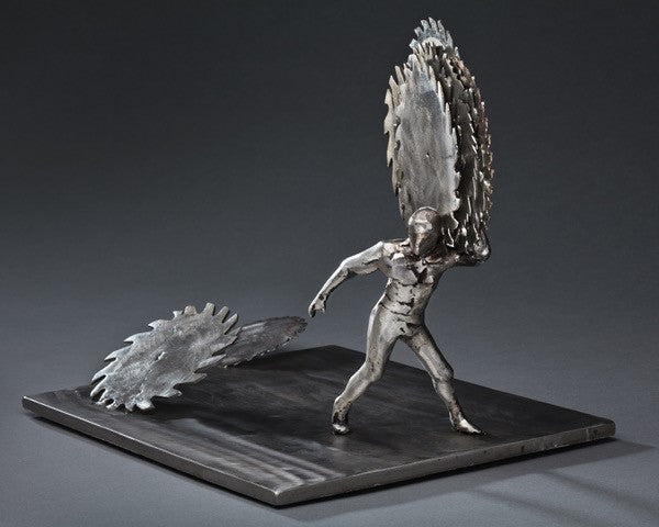 Peter McFarlane metal sculpture of human figure holding polished saw blades on his shoulder