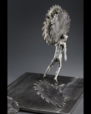 side view of Peter McFarlane metal sculpture of human figure holding polished saw blades on his shoulder