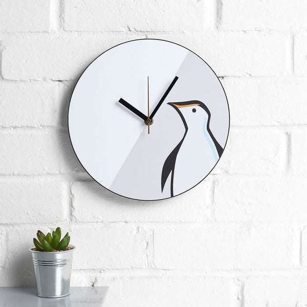 Penguin Wall Clock with Plant on a Kitchen Wall