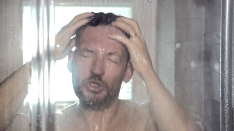 Man in shower before applying cologne