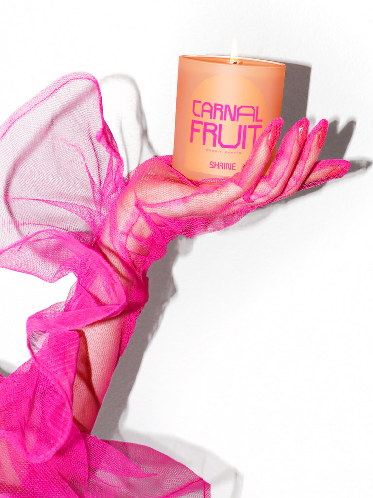 shrine carnal fruit monochromatic peach candle with neon pink text design in a neon pink mesh glove hand and neon pink nails shop shrine