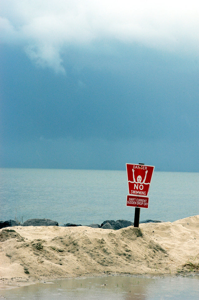 no swimming sign in sand in front of the gulf of mexico