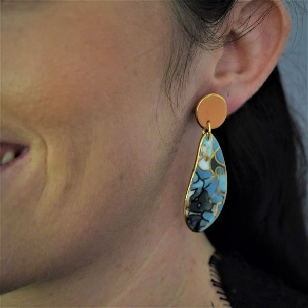 Double drop earrings with blue tops and earthy brown tones.