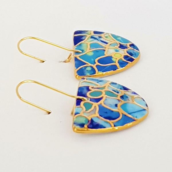 """D"" dangles in blue tones with 22 kt gold linework."