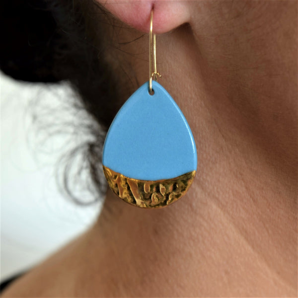 Drop earrings in teals with gold linework and white edge.