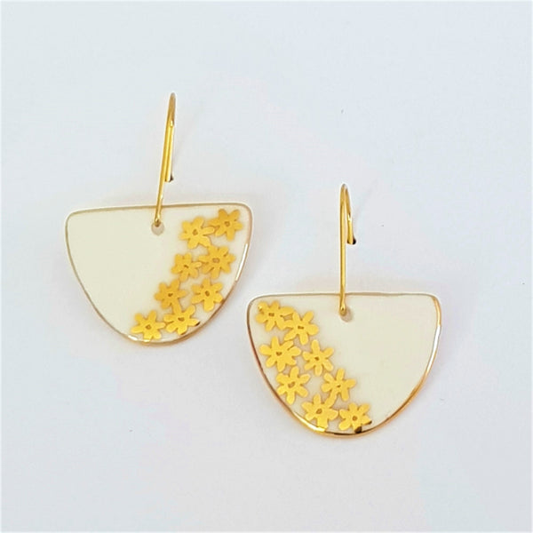 White porcelain D shaped dangle earrings with 22 kt gold daisies