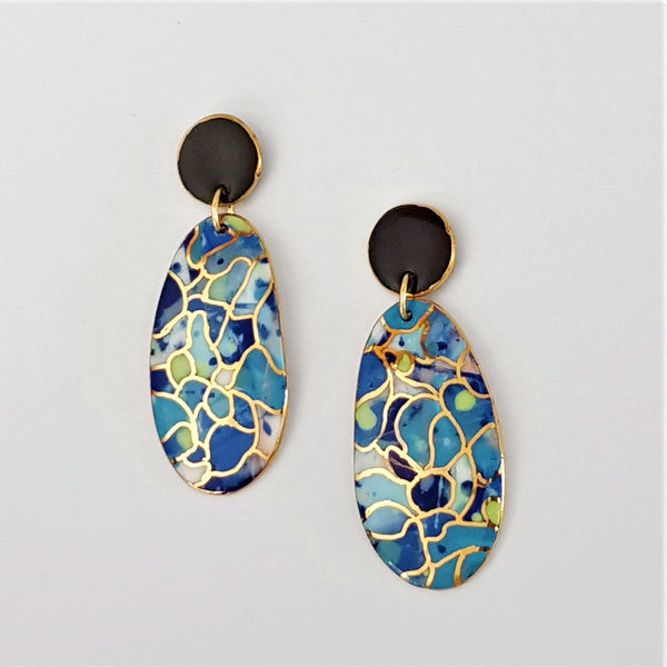 Double drops earrings. Multi blues and black tops with gold linework.