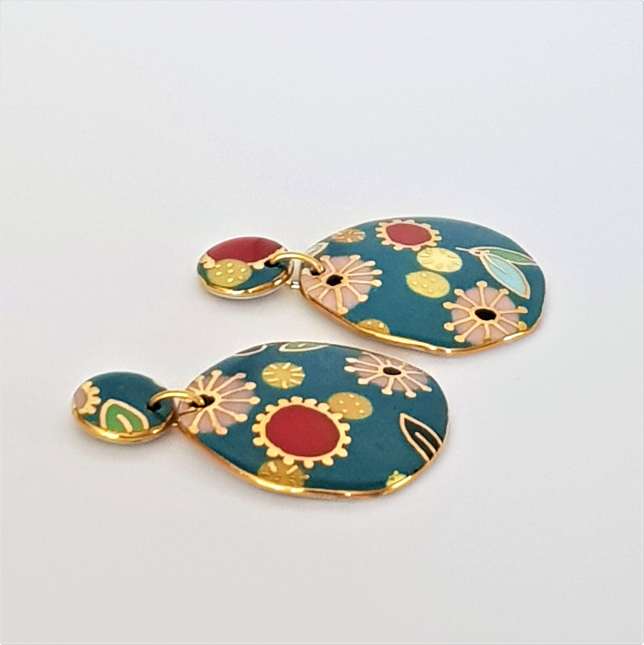 Turquoise double drop porcelain earrings with floral pattern and gold detailing.
