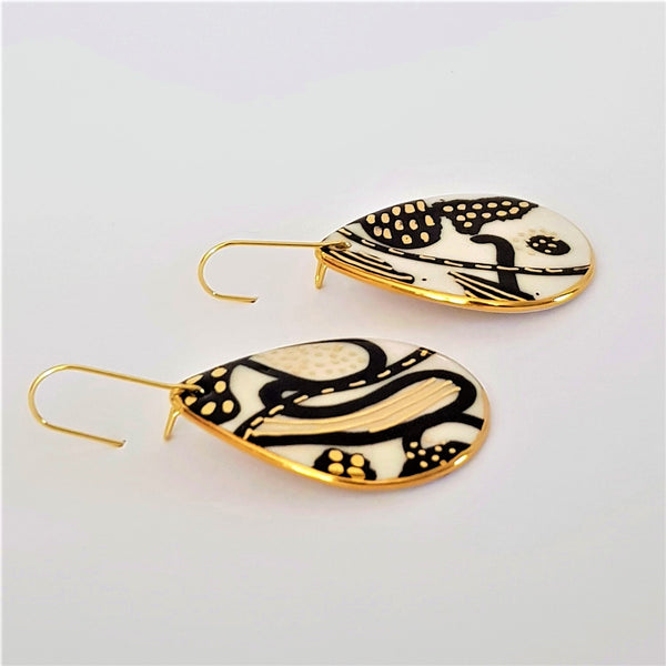 Black and white drop shaped porcelain earrings with unique 22 kt gold linework.