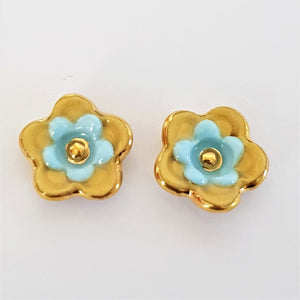Floral collective studs in mustard and light blue.
