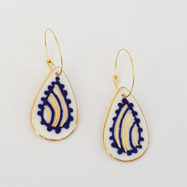 Porcelain paisley tear-drops is blue and gold on hoops.