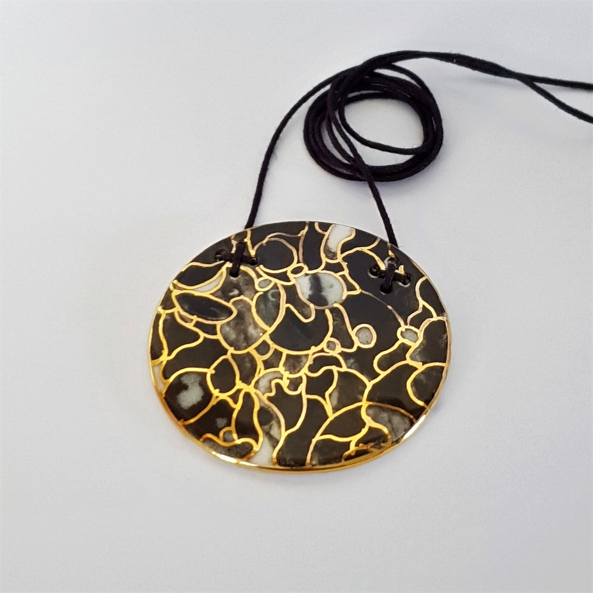 Large round pendant in black and gold abstract pattern