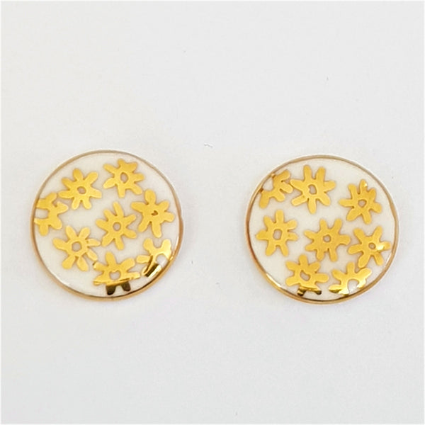 white stud earrings with gold flowers