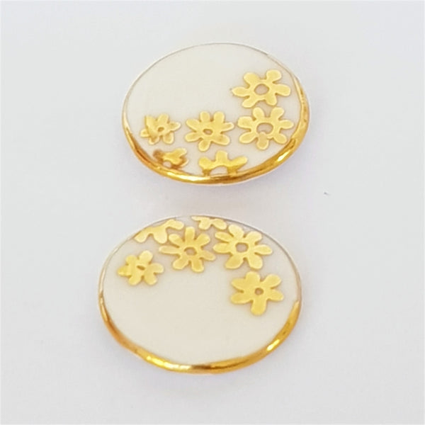 Round white stud earrings with 22kt gold daisies