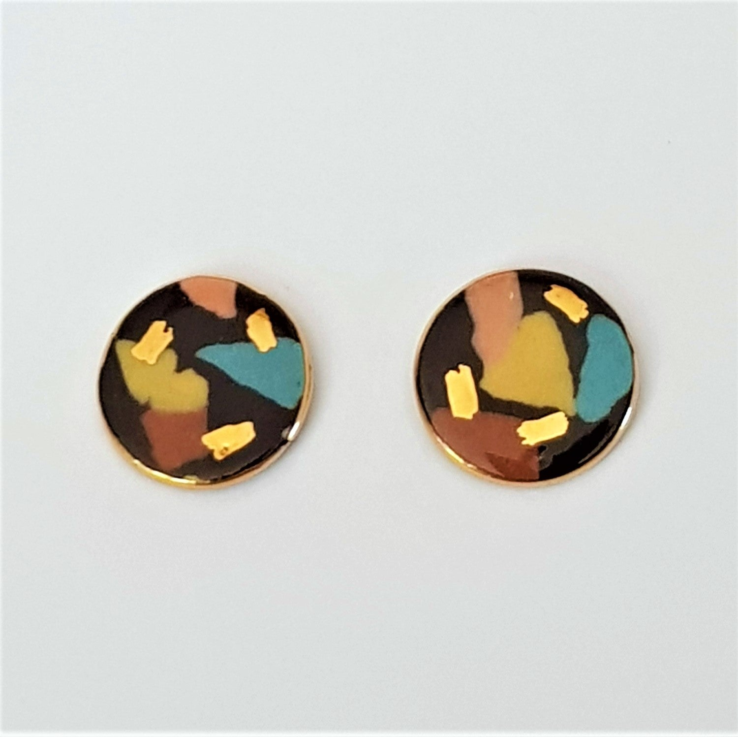 Round stud earrings in black with terrazzo effect and 22 kt gold.
