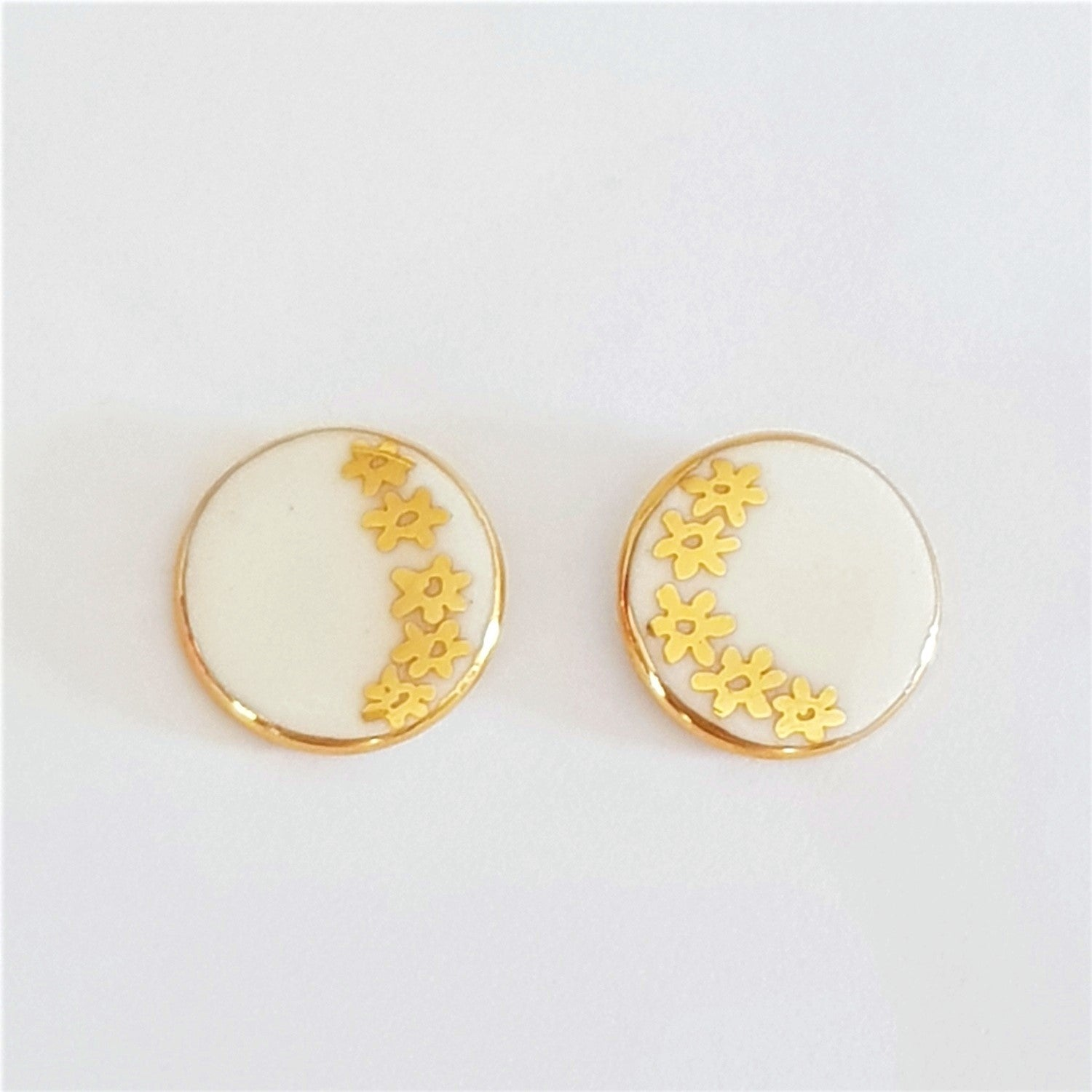Round stud earrings in white with gold daisies