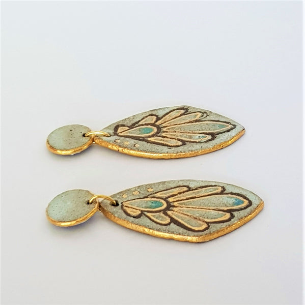 Elegant chocolate clay wings with a soft matte glaze and 22kt gold detailing.