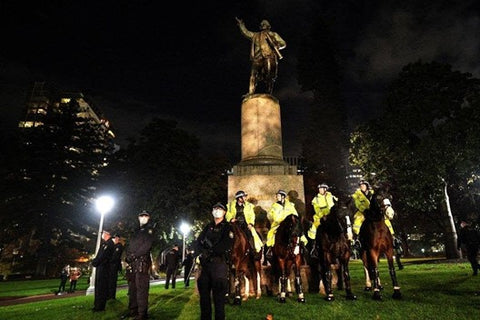 Police officers standing guard around statue of James Cook in Sydney, 2020
