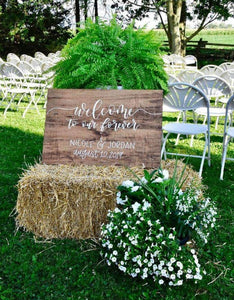 welcome to our forever calligraphy on wood wedding sign staged with florals and hay bales