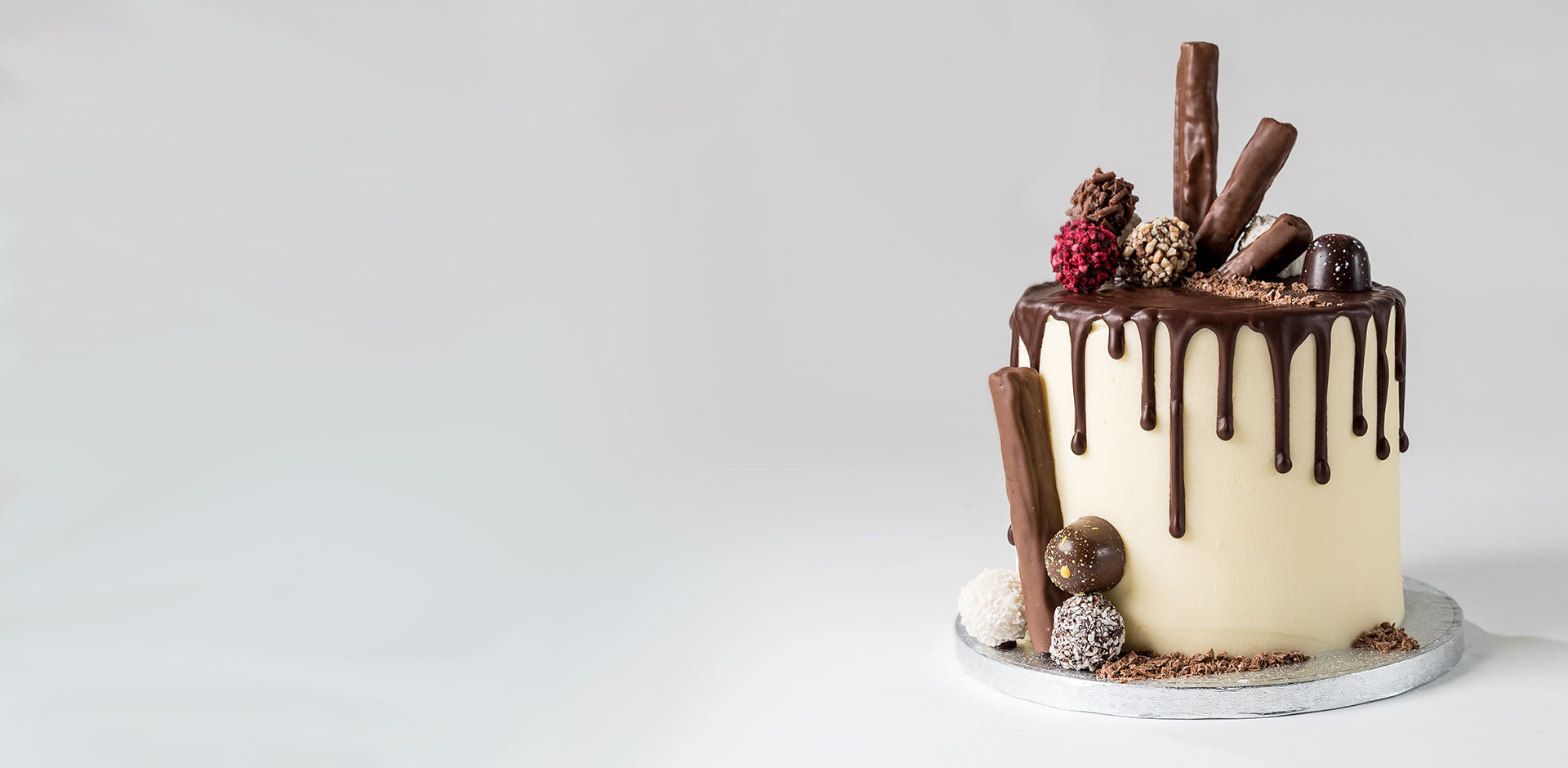 Photograph of a vanilla flavour cake with a chocolate ganache drip effect from ChocoCake positioned to the right