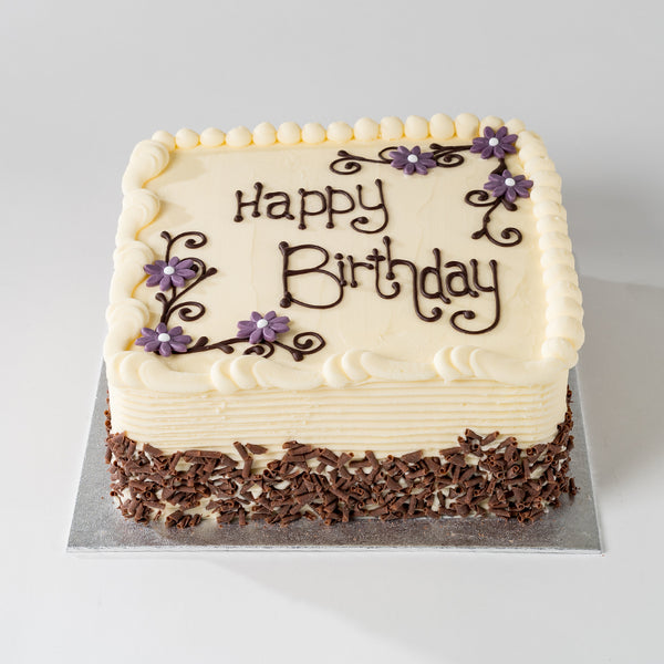 Photograph of a Happy Birthday Vanilla Buttercream cake with chocolate decoration and personalisation available to order at ChocoCake