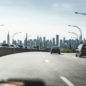 View from a yellow taxi cab from the road going in to New York City.