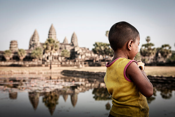 Young girl walking in front of the Angkor Wat Temple complex.