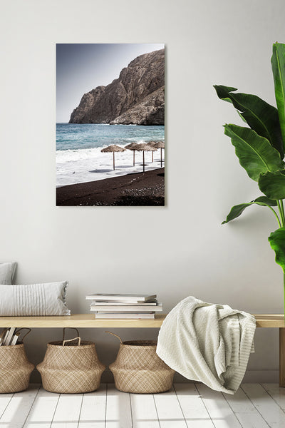 Vertical photo of Black Sand Beach in Santorini shown on a white wall in a modern interior.