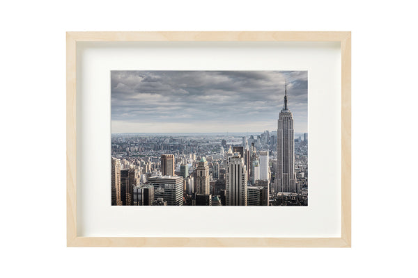 Empre State Building seen from the top of Rockefeller Centre, New York City. Horizontal photo shown in a boxed frame.