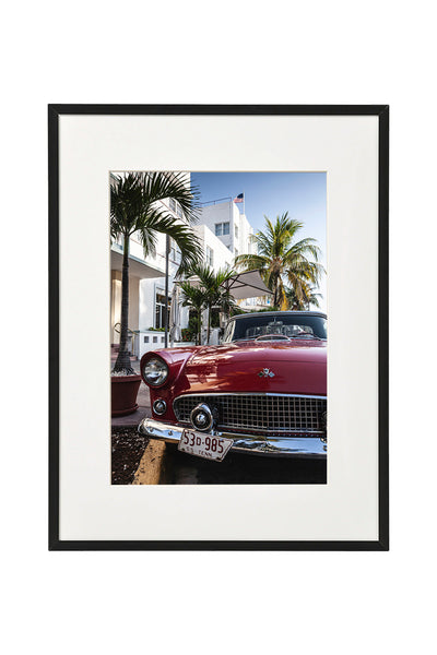 Vintage red Oldtimer car, parked in front of a hotel in Ocean Drive. Vertical photo shown in a normal frame.